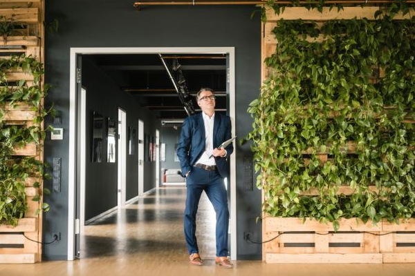 Man in office with plants climbign walls