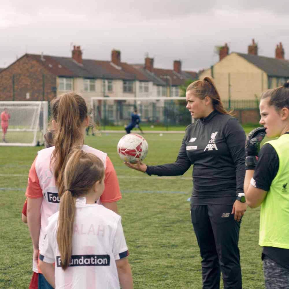 Liverpool Football Club community coach running a session with children