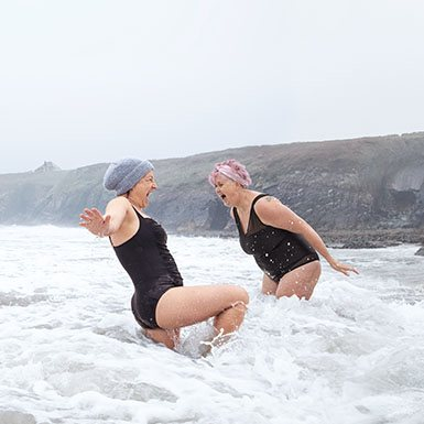 Two ladies from The Bluetits Open Water Swimmers in the sea off the Pemrokeshire coast