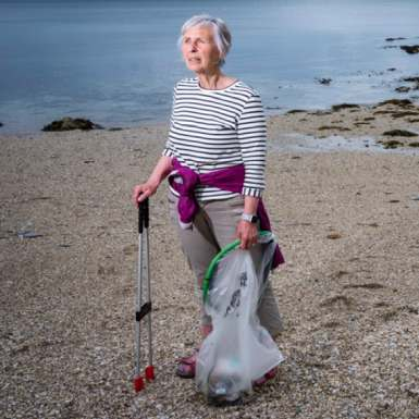 Action Nan on beach with litter picker and recycling bag