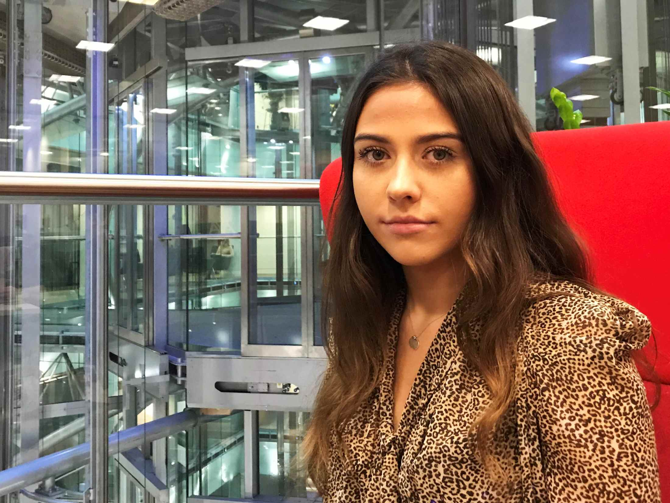 Mia Simpson, PR Apprentice, sat at in a red chair in AXA's London Office on Old Broad Street