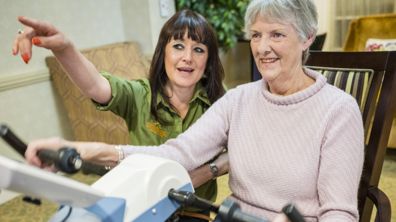 Dementia sufferer Anne sat on Motiview bicycle with care worker Zoe by her side