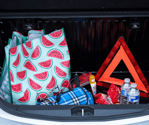 Car boot containing a rug, sunglasses, bottles of water, crisps, water and a warning triangle