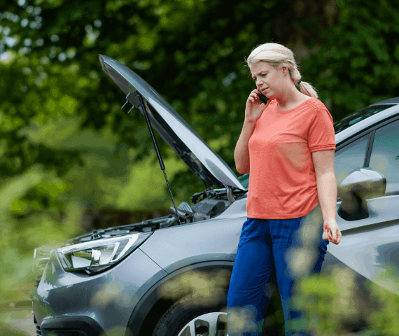 Woman stood by side of road with bonnet up on the phone calling breakdown recovery