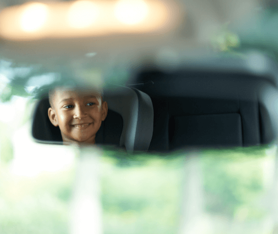 Child sat in car seat as viewed in driver's mirror