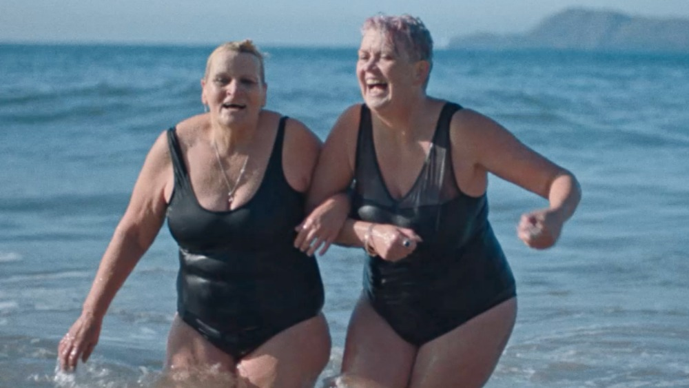 Two women from the Bluetits Cold Water Swimming Club in the sea wearing black bathing suits