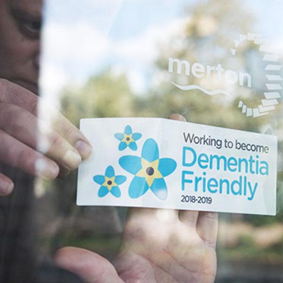 "A person holding a card that reads, ""Working to become dementia friendly 2018 to 2019"