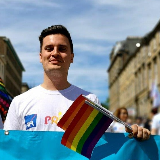 AXA employee at Pride event holding rainbow flags