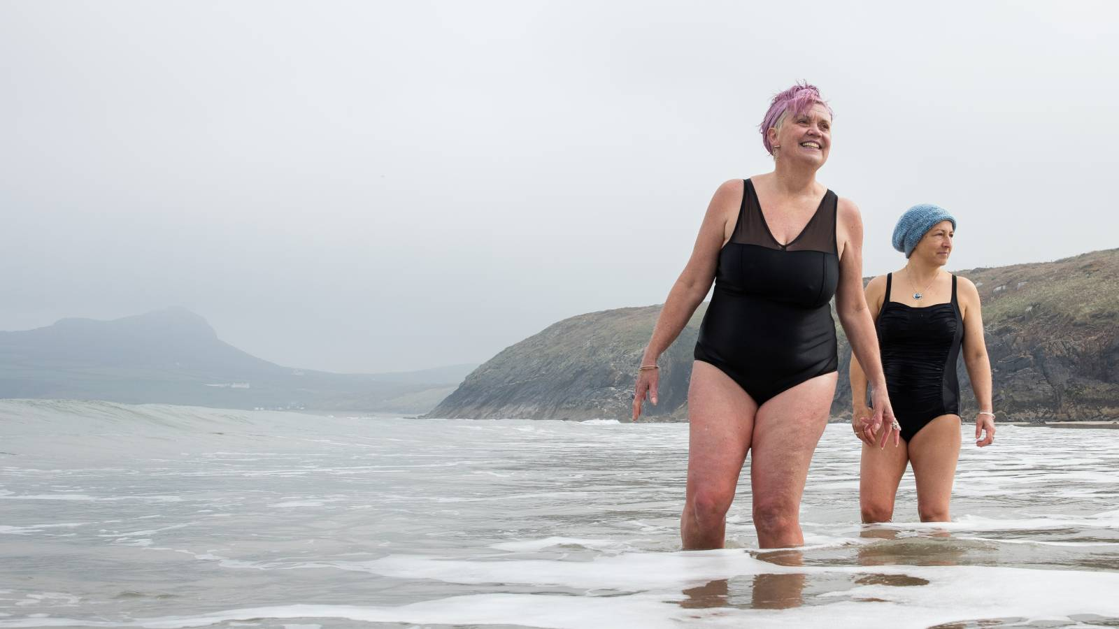Sam and Sian, from the Bluetits cold water swimmers, standing in the sea in West Wales