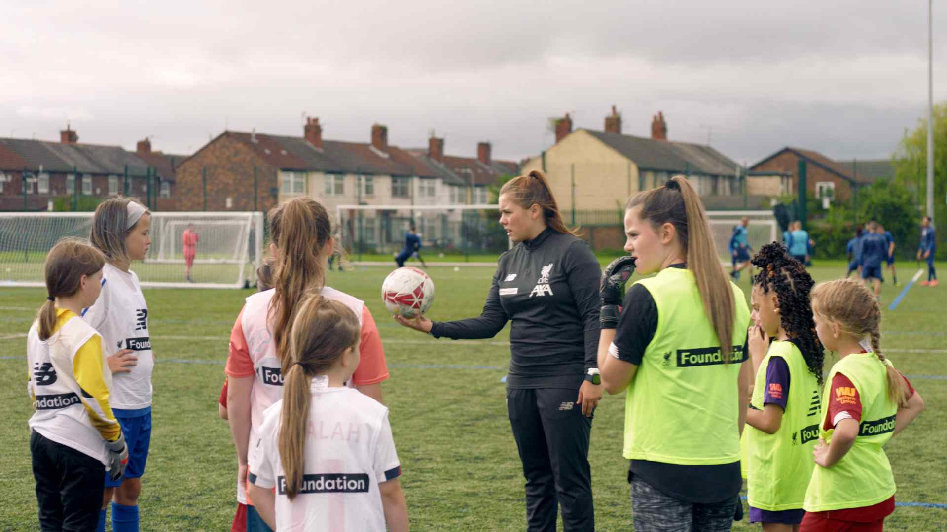 Liverpool Football Club Foundation coach talking to young girls as part of the Head Coaches programme in partnership with AXA UK