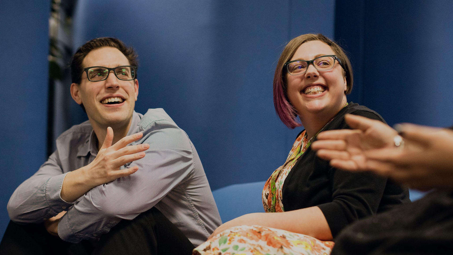 Man and woman both wearing glasses sat on sofa with big smiles on their faces