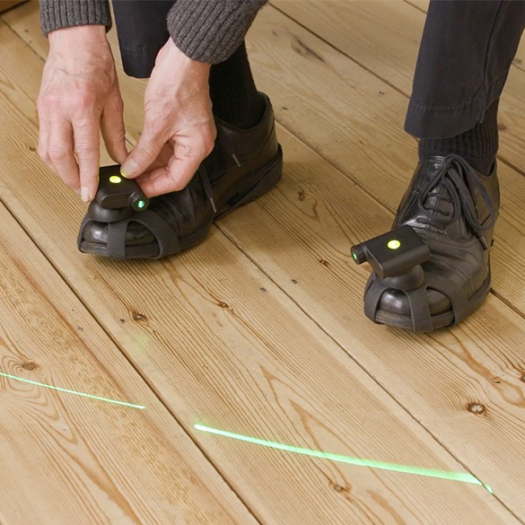 Man with Parinkson's wearing shoes with laser gadget attached for guidance