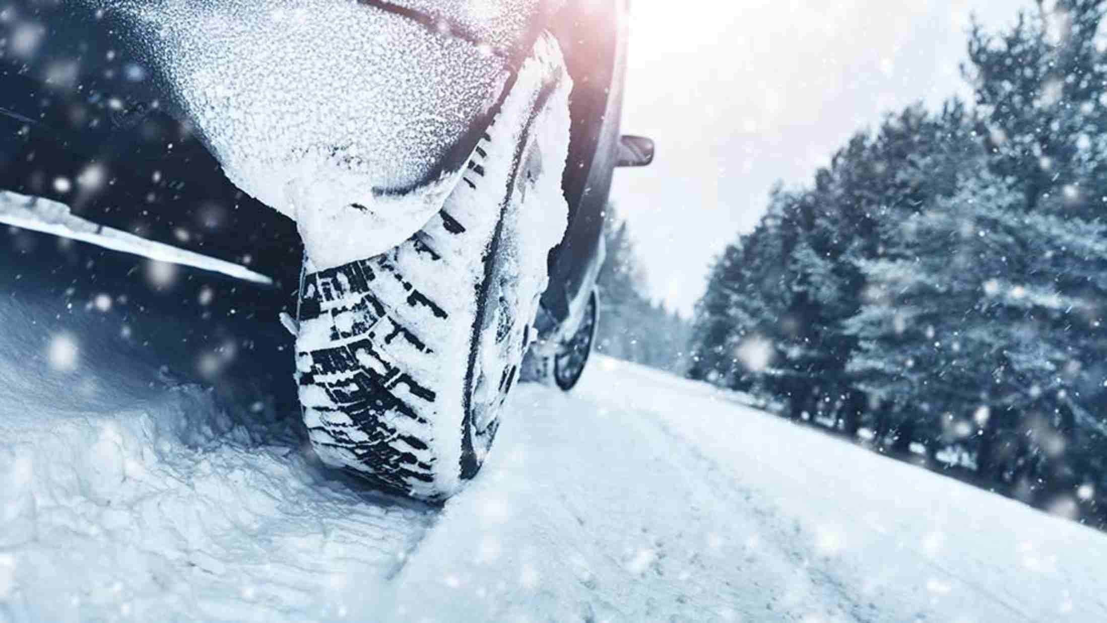 Close up of a car tyre on a road covered in snow