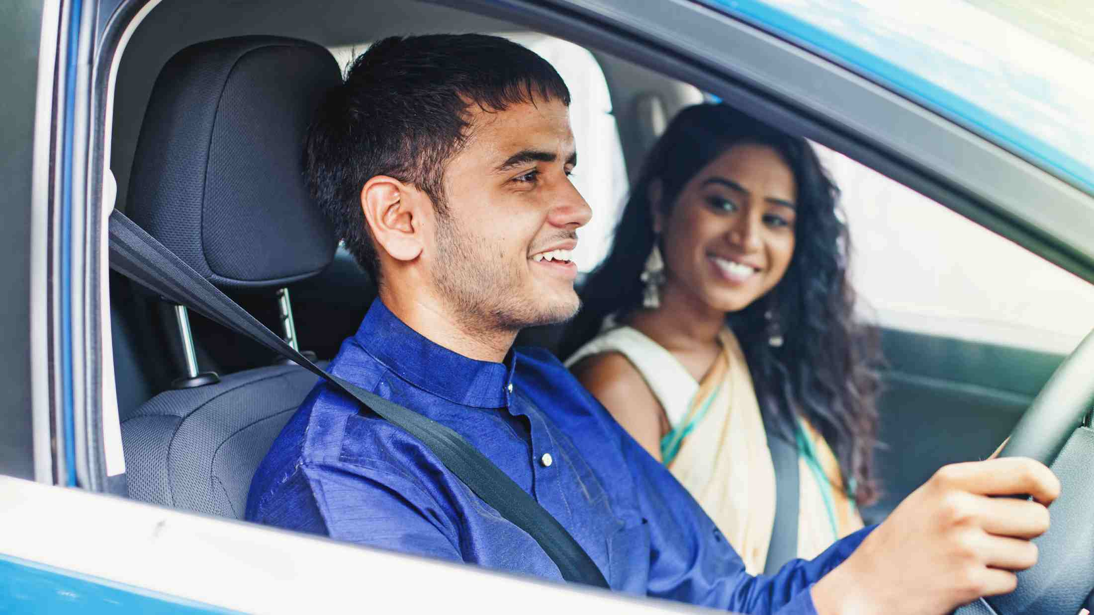 Male driver giving a ride to a young woman in a blue car