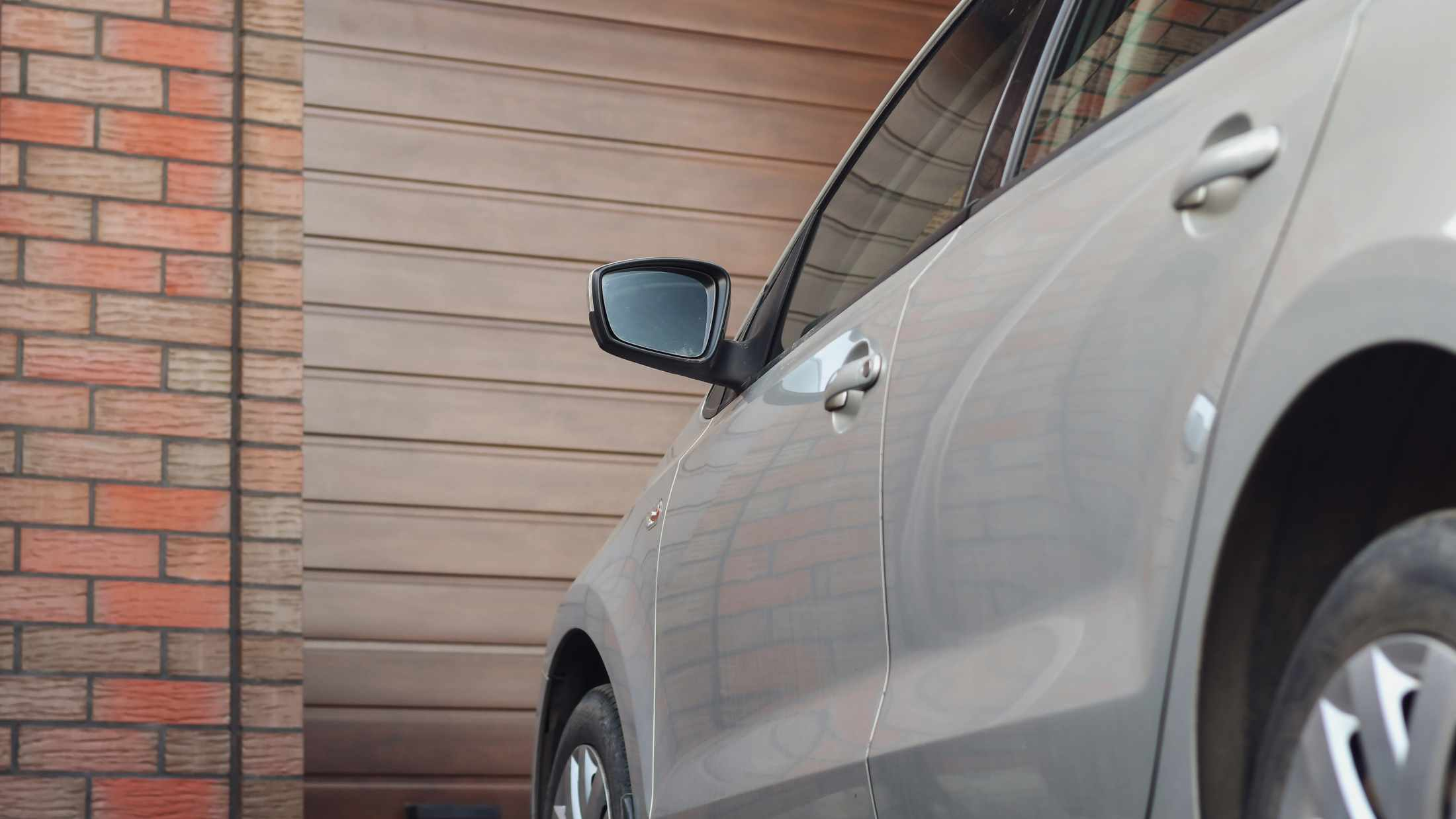 Silver car parked on driveway in front of garage with a brown door