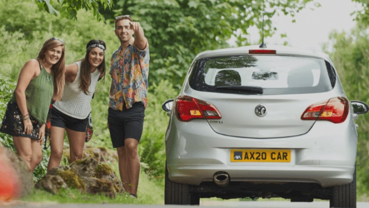 Two young women and a man stood by side of a silver car