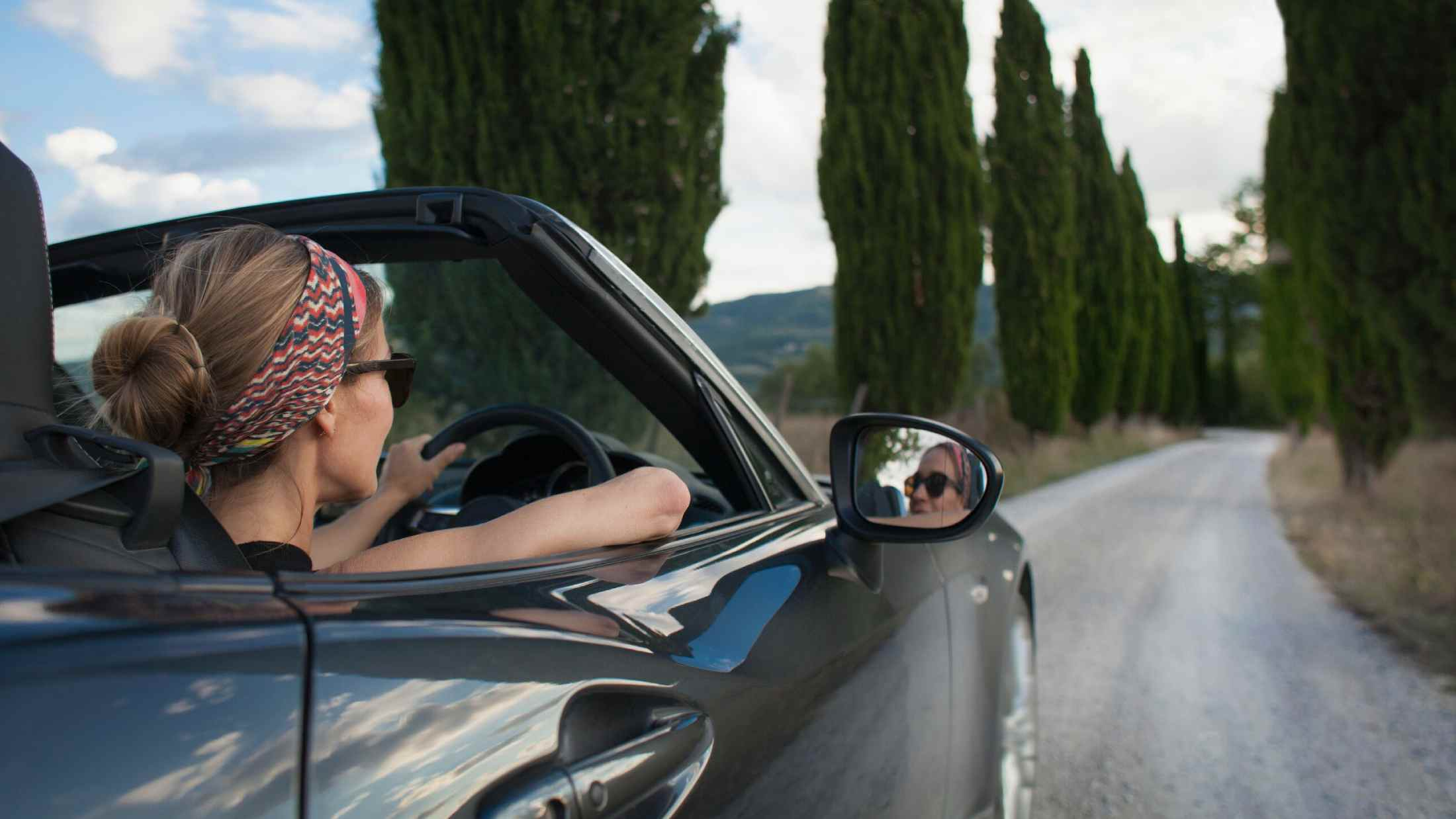 Woman driving convertible car on Tuscan country road