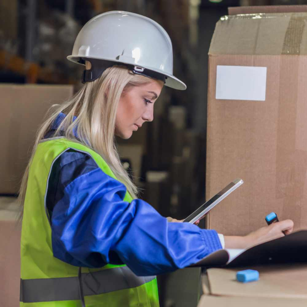 Woman wearing hi-vis jacket and hard hat holding phone and highlighter pen surrounded by cardboard boxes