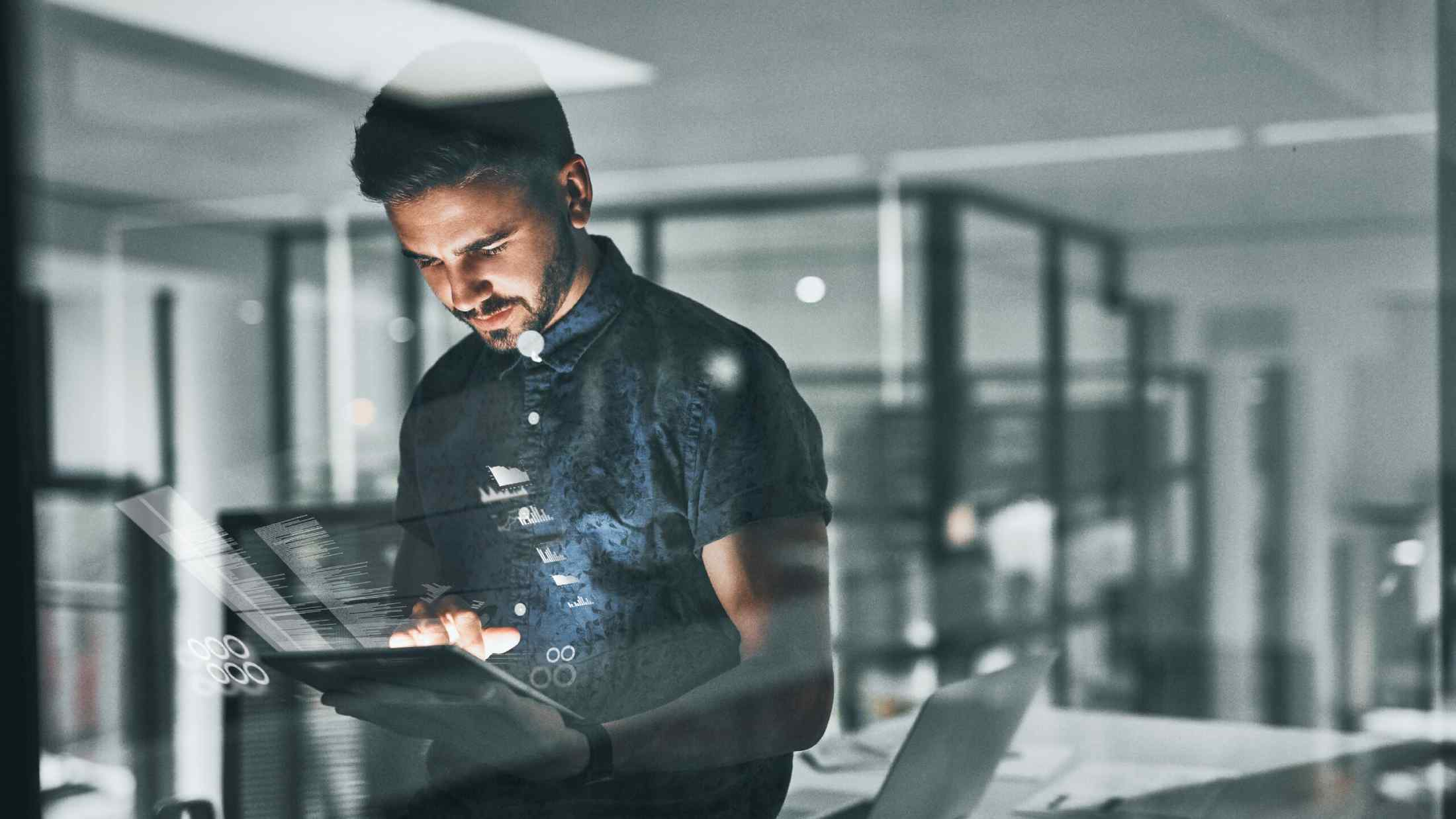 Man working on tablet in office with reflection in window
