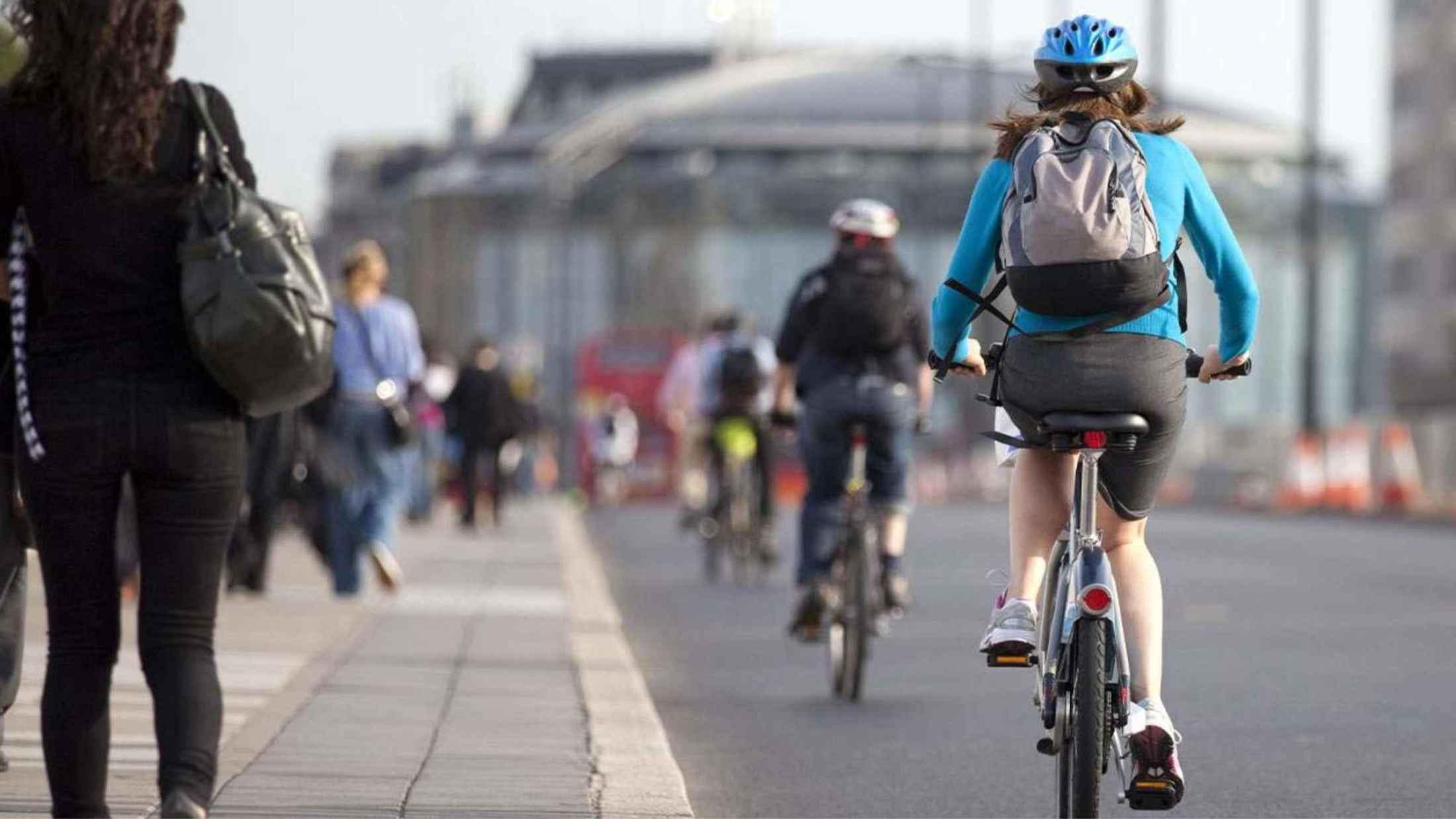 Woman wearing blue top and blue helmet cycling towards central London