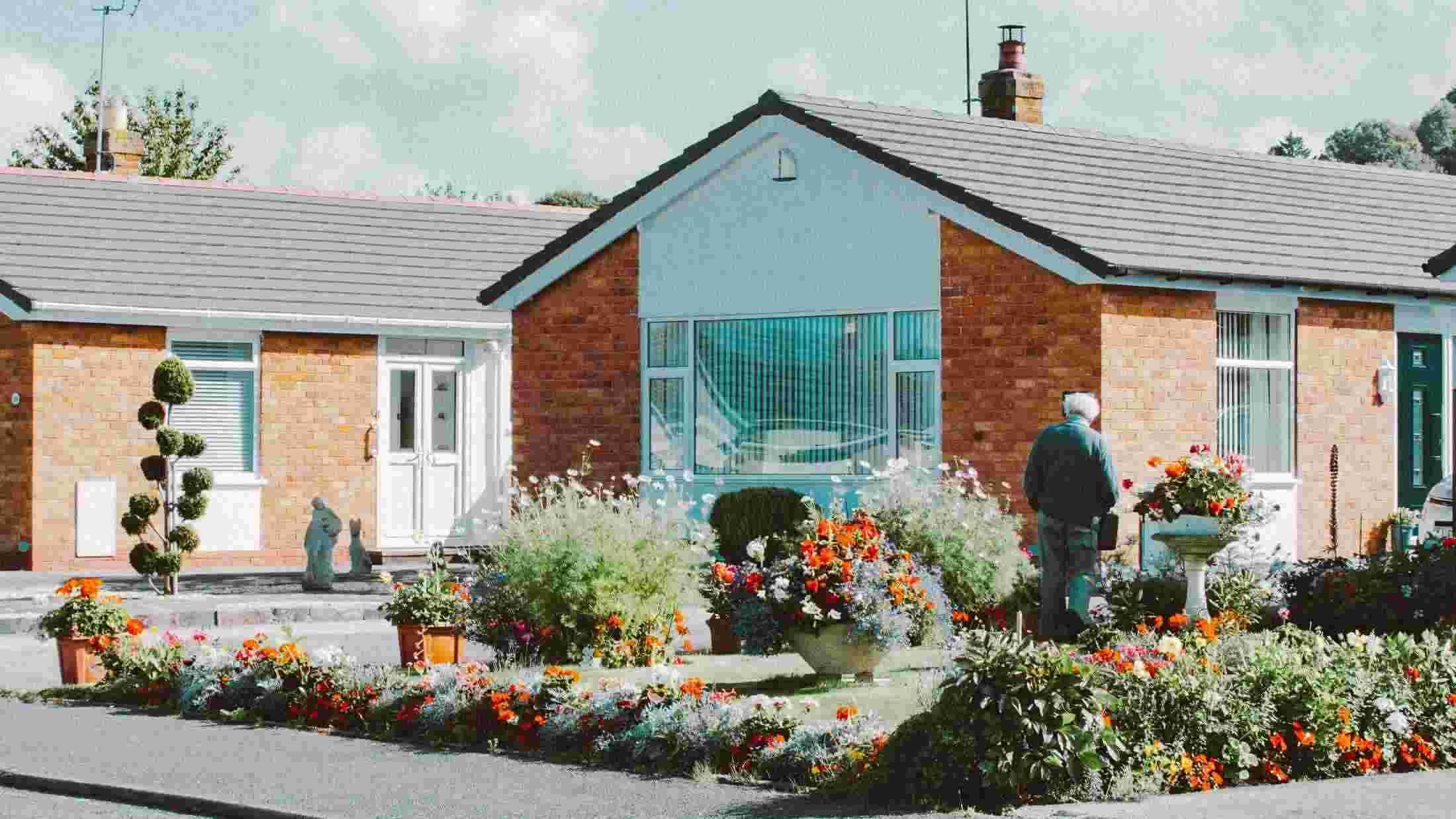 Bungalow with elderly man in front garden