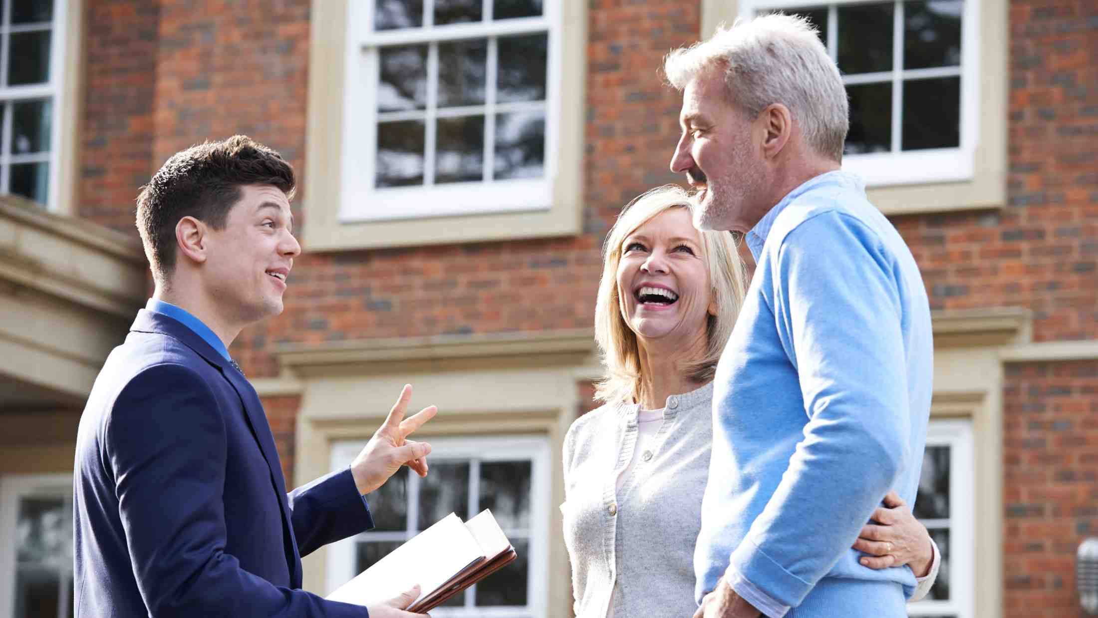 Man and woman with estate agent outside home