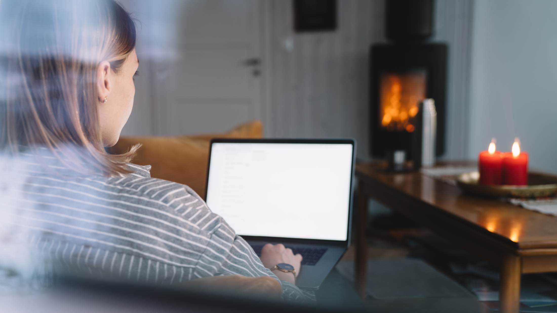 Woman working on laptop in front of open fire
