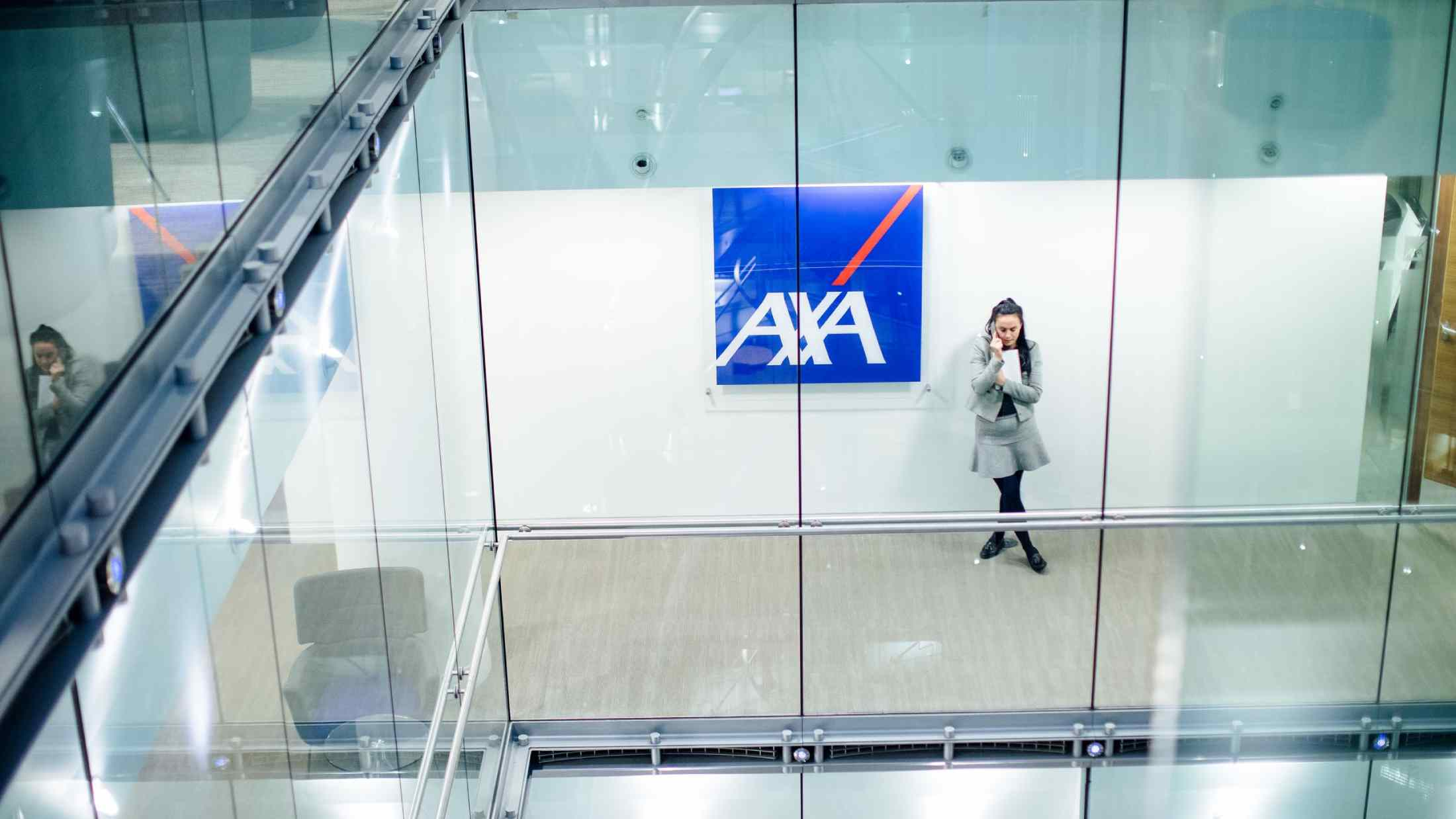 AXA employee talking on mobile phone while stood beside logo on wall of Old Broad Street office