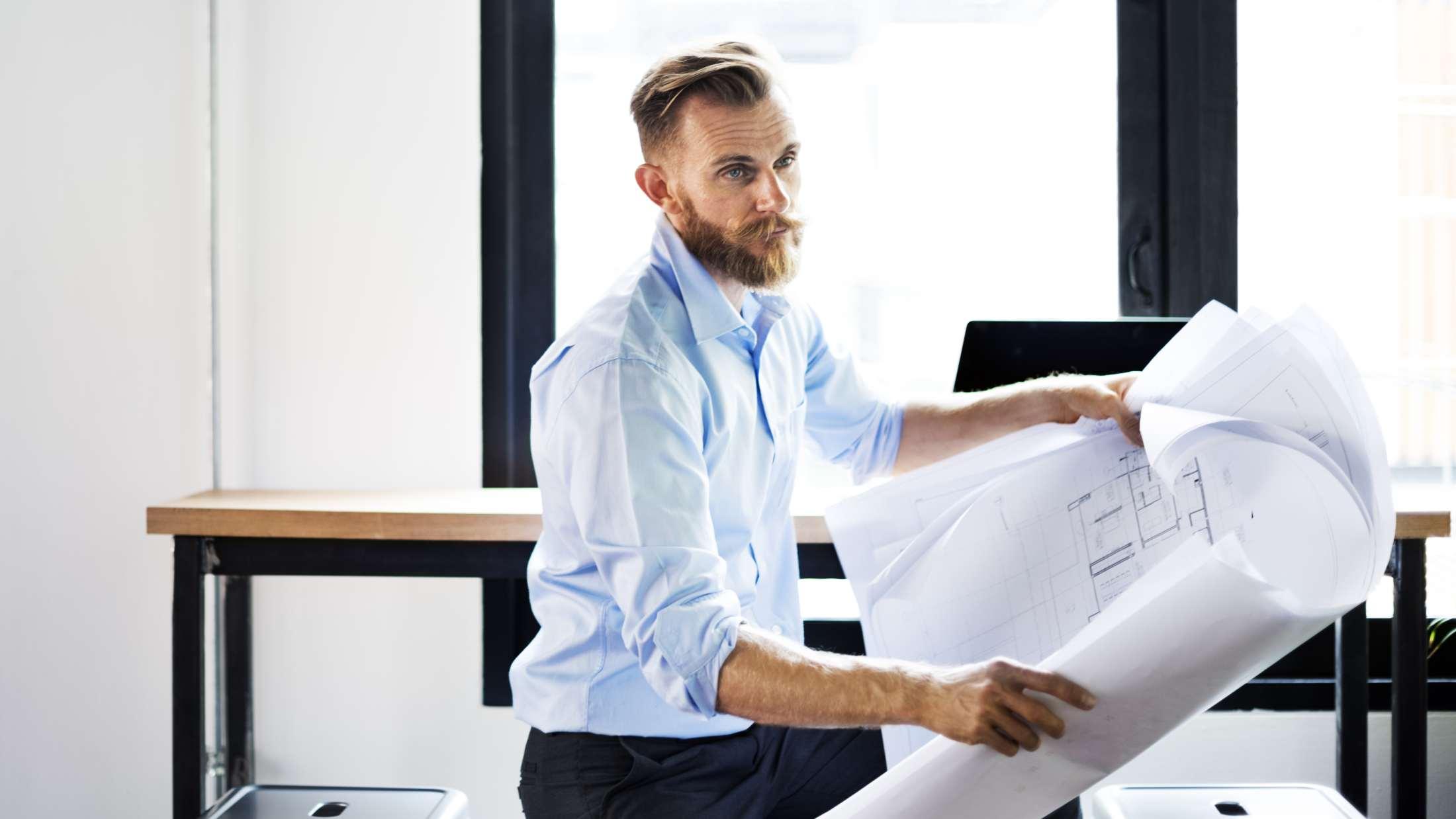 Man holding blueprint plans